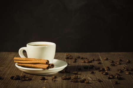 white cup about coffee and the scattered coffee beans on a wooden backgroundwhite cup about coffee and the scattered coffee beans on a wooden background. With copy space
