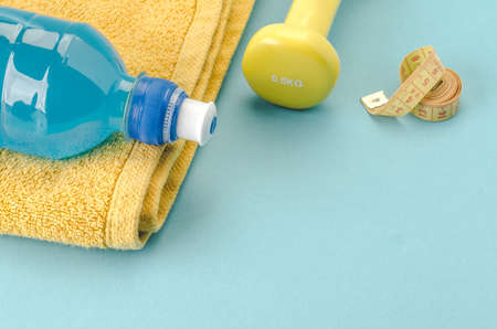 Fitness concept with dumbbell, towel, measure tape and bottle/yellow dumbbell, towel, measure tape and bottle on a blue background. selective focus. Copy space