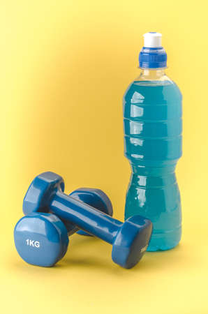Fitness concept with dumbbells and bottle/blue dumbbells and bottle on a yellow background. Stock fotó