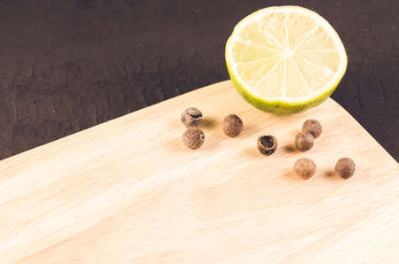 lime segment and spices on a empty cutting boardlime segment and spices on a empty cutting board on a dark background Banco de Imagens
