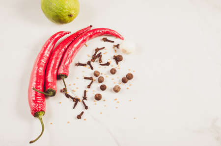 spices, chili pepper and lime on a white marble background. Top view. Copy space