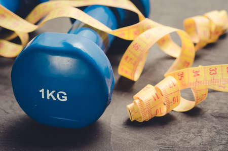 Blue dumbbells and yellow centimeterfitness concept with blue dumbbells and yellow centimeter on a dark background. Close up Stockfoto