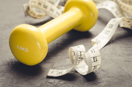fitness concept with yellow dumbbell and measuring tapefitness concept with yellow dumbbell and measuring tape on a dark background.