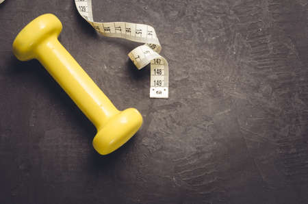 fitness equipment on a dark backgroundfitness equipment with yellow dumbbell and measuring tape. Top view and copy space