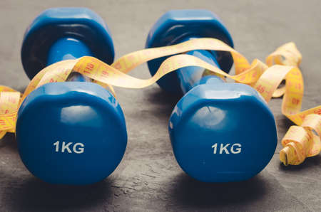 Sports equipment on a dark backgroundSports equipment with Blue dumbbells and yellow measuring tape. Selective focus Stock Photo