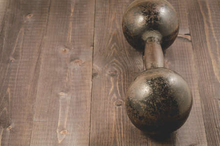 old iron dumbbellold iron dumbbell on dark wooden background with copy space 版權商用圖片