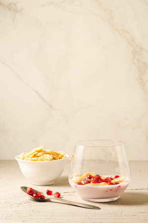Homemade yogurt with pomegranate and flakesHomemade yogurt with pomegranate and flakes on a white background with copy space