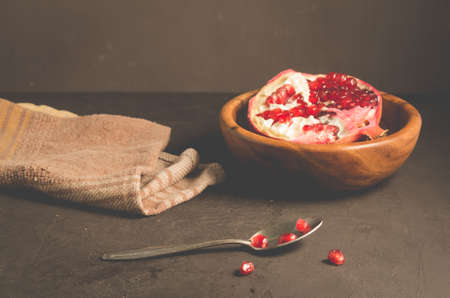 cut into pieces red garnet in a wooden bowl on the tableparts of pomegranate in a wooden bowl and a spoon against a dark background, selective focus Stock Photo