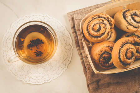 glass cup of tea and rolls with poppy in a wooden basket/glass cup of tea and rolls with poppy in a wooden basket on a white table. Top view Zdjęcie Seryjne