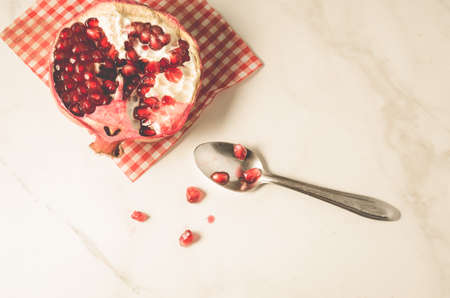 parts of pomegranate on a red napkin and a spoonparts of pomegranate on a red napkin and a spoon on a white table, top view Imagens