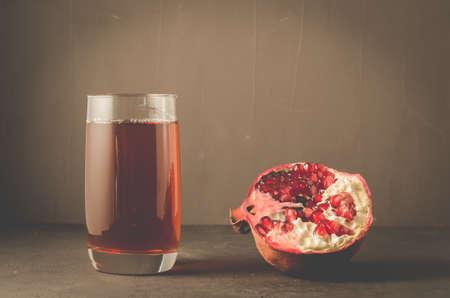 Pomegranate fruit and juice in glassPomegranate fruit and juice in glass on dark background Reklamní fotografie