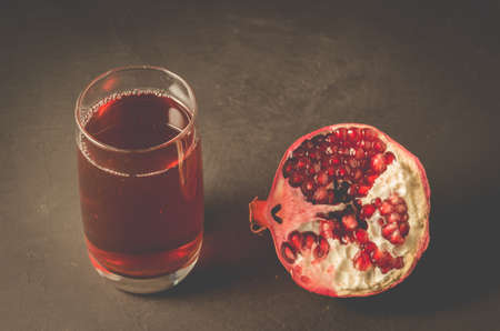 Ripe pomegranate, a piece and a glass of juiceRipe pomegranate, a piece and a glass of juice on a dark background, selective focus