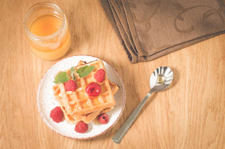 Waffles With raspberry in plate. BreakfastHomemade waffles with raspberry in plate, honey on a wooden table, top view