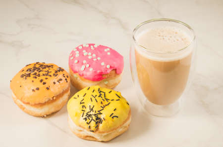 donuts in glazes and a glass of a cappuccino/donuts in glazes and a glass of a cappuccino on a white table. Selective focus