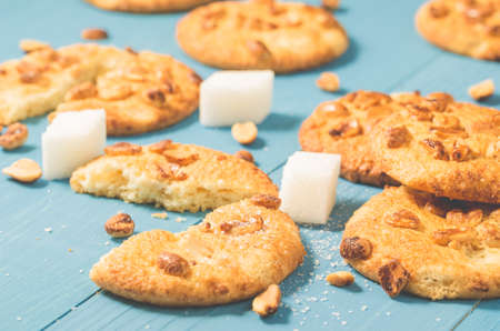 Tasty cookies with nuts and lump sugar on a blue wooden Archivio Fotografico