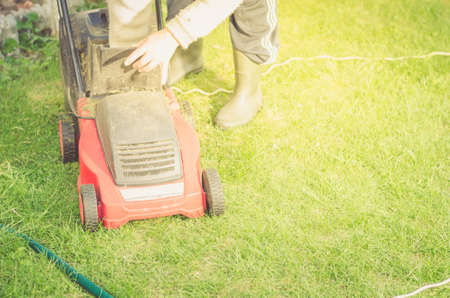 lawn mower is cleaned from a grasslawn mower is cleaned from a grass. Copyspace