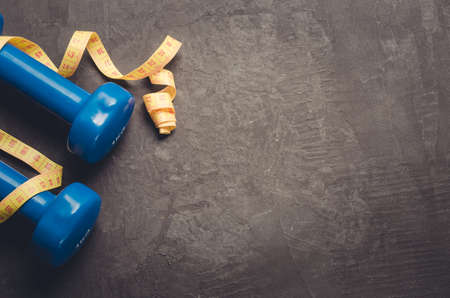 Sports equipment on a dark background/Sports equipment with Blue dumbbells and yellow measuring tape. Top view and copy space