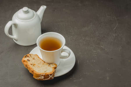 White tea cup and teapot with a pastries piece on dark stone table. Copyspace