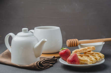 Delicious breakfast with tea, honey and wafers decorated with fresh strawberry on a stone table. Selective focus