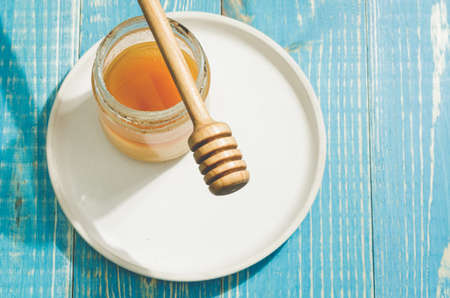 jar of honey and honey dipper in a white bowl on a blue wooden background, top view and copy space