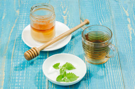 tea with mint and honey on a wooden blue table. Selective focus image