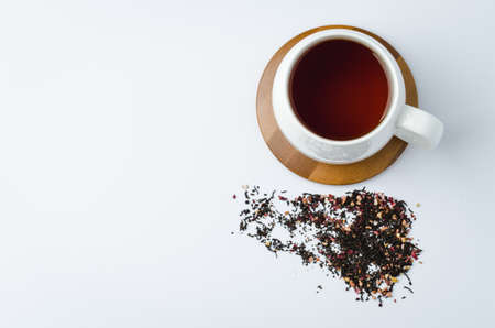fruit tea in a white mug on a bamboo support and dried tea isolated on white background. Top view and copyspace