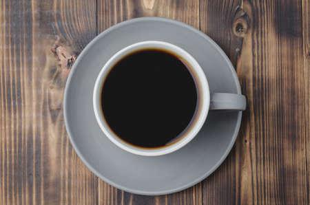 Grey cup with black coffee on on dark wooden table. Top view. Coffee break. Foto de archivo