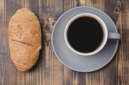 Coffee break. Grey cup with black coffee and croissant on dark wooden table. Top view.