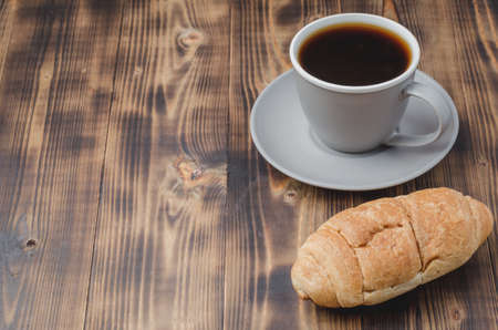 Coffee break. Grey cup with black coffee and croissant on dark wooden background with copy space