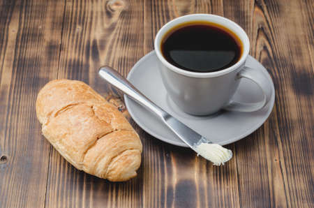 Coffee break with croissant butter knife and cup of black coffee on a dark wooden table. Foto de archivo