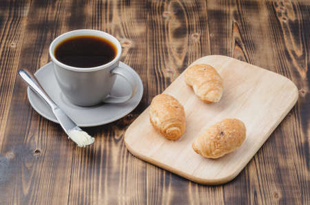 Grey cup with black coffee and wooden tray with croissants on wooden table.