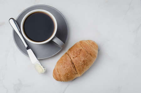 Coffee break with croissant butter knife and cup of black coffee on a white stone table. Top view and copyspace