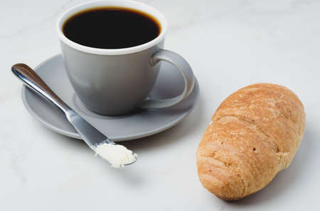Coffee break with croissant, butter knife and cup of black coffee on a white stone table.  Foto de archivo