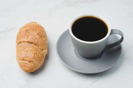 Coffee break. Grey cup with black coffee and croissant on white stone background.