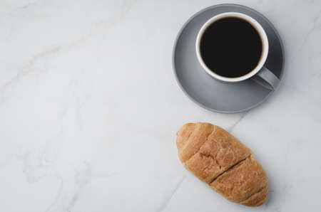 Coffee break. Grey cup with black coffee and croissant on white stone background. Top view and copyspace
