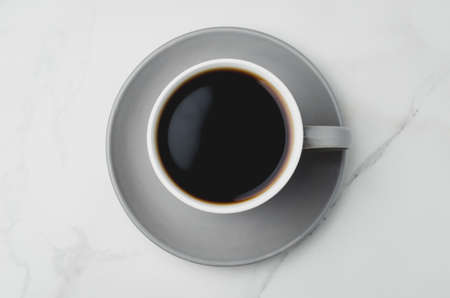 Grey cup with black coffee on on white background. Top view. Coffee break. Foto de archivo