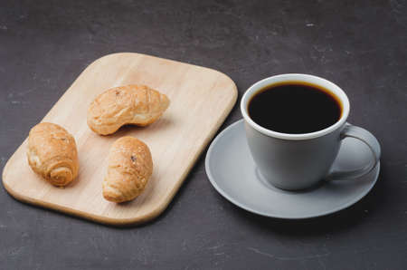 Grey cup with black coffee and wooden tray with croissants on dark table. Coffee break.