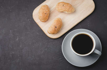 Grey cup with black coffee and wooden tray with croissants on dark table. Top view and copyspace. Coffee break. Foto de archivo