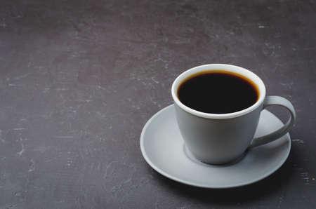 Grey cup with black coffee on on dark table. Selective focus and copy space. Coffee break. Foto de archivo