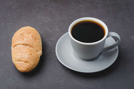 Coffee break. Grey cup with black coffee and croissant on dark background.