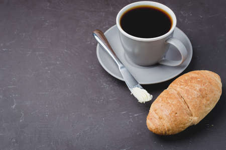 Coffee break with croissant, butter knife and cup of black coffee on a dark stone background. Copyspace