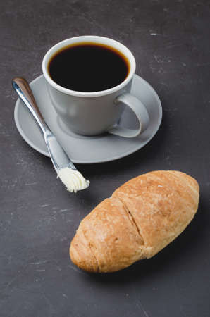 Coffee break with croissant, butter knife and cup of black coffee on a dark table. Foto de archivo