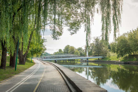 Bike path in the park with green beautiful trees along the river. Beautiful summer landscape. Foto de archivo