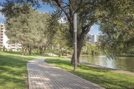 Walkway in the city park for walks along the river. Beautiful landscape of summer. Outdoor walks Foto de archivo