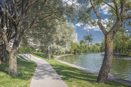 Walkway in the city park along the river. Beautiful landscape of summer. Foto de archivo