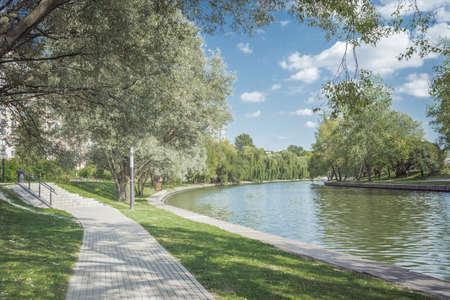 Walkway in the park along the river. Beautiful landscape of summer. Foto de archivo