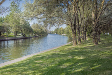 River in the city park. Trees along the embankment. Beauty nature scene. Foto de archivo
