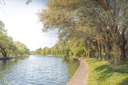 Park along river and green trees. Beautiful landscape.  Foto de archivo