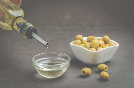 Olive oil pouring from bottle in bowl and fresh olives in ceramic plate and on dark stone table. Foto de archivo