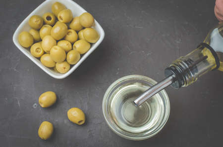 Olive oil pouring from bottle in bowl and fresh olives in ceramic plate and on dark stone table. Top view. Foto de archivo